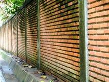 Ancient brick wall beside way after rain fall Royalty Free Stock Image