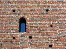 Ancient brick wall with window. Old brick wall with window and visible damage, erosion - different colour bricks Stock Images
