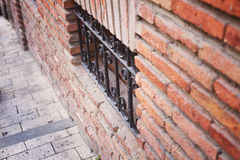 Ancient brick wall and window locked with metal bars.  Royalty Free Stock Image