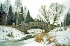 Ancient bridge over iced river Stock Photos