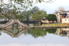 Characteristic ancient bridge at the riverside in water village Hongcun (Unesco), China. Ancient bridge in the village Hongcun along the lake in the province Stock Photography