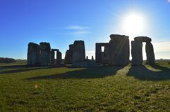 Stonehenge casting a shadow in the sun. Ancient British site, Stonehenge silhouetted against the sky with the sun shining behind Stock Images