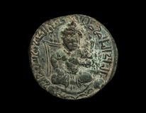 Ancient bronze islamic coin with seated figure isolated on black. Macro shot stock photography