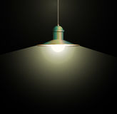 Ancient bronze lamp hanging. Big and empty space illuminated on the dark wall. Royalty Free Stock Photo