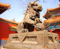 Ancient bronze lion (Beijing, China). Ancient bronze lion and red chinese pavilliones in famous Lama Temple (Beijing, China stock photos