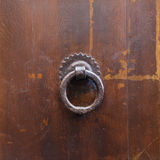 Ancient bronze round knocker on old brown door Royalty Free Stock Photography