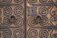 Ancient brown wooden door with metallic ornaments Royalty Free Stock Photo