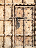 Ancient brown wooden door with metallic ornaments and a big bolt Royalty Free Stock Photography