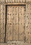 Ancient brown wooden door with metallic ornaments on a wooden wall Royalty Free Stock Images