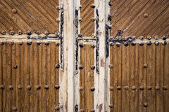 Ancient brown wooden door with metallic ornaments on a wooden wall Stock Photos