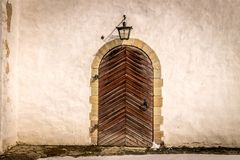 An ancient brown wooden door with an old wall lamp. stock photos