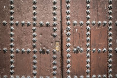 Ancient brown wooden door with star shaped metallic ornaments Stock Photos