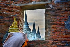 Ancient buddha and 3  big standing bell shape pagoda in the same line in Ayutthaya historical park, the famous ancient temple in T Stock Photos