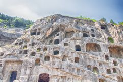 Longmen Grottoes Scenic Area Luoyang China. Ancient Buddha carvings and caves within longmen grottoes in Luoyang China in Henan Province on a sunny day stock photography