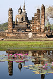 Ancient Buddha Reflecting. An ancient statue of Buddha reflects in the lotus fill pond on a clear day in modern day northern Thailand Stock Photography