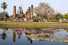 Ancient Buddha Reflecting. An ancient statue of Buddha reflects in the lotus fill pond on a clear day in modern day northern Thailand Stock Images