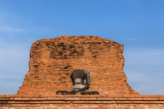 Ancient buddha sandstone statue without head front ruins bricks wall Royalty Free Stock Photography