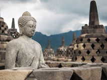 Ancient Buddha Statue at Borobudur, Indonesia. An ancient Buddha statue surrounded by stupas at Borobudur, the world's largest Buddhist monument, Java, Indonesia Stock Photo