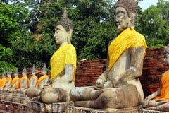 Ancient statues of meditating buddha sitting, at Wat Yai Chaimongkol old temple in Ayutthaya, Thailand stock photos