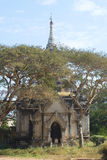 Ancient Buddhist pagoda among trees on a sunny day. Bagan, Burma Royalty Free Stock Photo