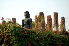 Buddhist Statue in Flower Garden Bathed in Light. An ancient buddhist statue sits in deep meditation with temple ruins behind him and pink flowering bushes in Royalty Free Stock Photography