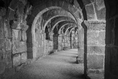 Ancient building corridor, columns and arches. A black and white photo of old ancient building corridor, made of stone columns and arches Royalty Free Stock Photo