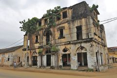 An ancient building in a street of grand bassam in ivory coast. Building in ruin in a street of grand bassam in ivory coast. plants are growing among the stones stock photos