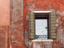 Ancient building in venice with red faded painted wall. And green shutters on a window stock photo