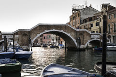 Ancient buildings and boats in the channel in Venice Stock Images