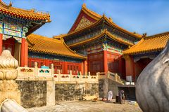 Ancient buildings in the Forbidden City, China. Ancient buildings of the Forbidden City, famous Imperial Palace Complex in Beijing. A worker makes some Royalty Free Stock Images