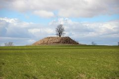 Ancient Burial Mound Hill with Dramatic Clouds Royalty Free Stock Photos