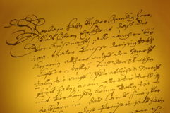 Ancient Caligraphy. Beautiful ancient handwriting on a yellow paper. It is like a piece of artwork. It is absolutely freely and spontanousely written and reminds royalty free stock photo