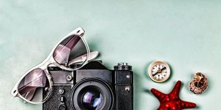Ancient camera, compass and sea souvenirs on a blue background. Royalty Free Stock Photo