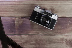 The ancient camera. The camera, film, lie on a wooden table the top view royalty free stock image