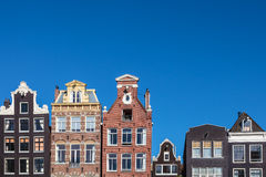 Ancient canal houses in the Dutch capital city Amsterdam. Row of ancient canal houses in the Dutch capital city Amsterdam against a blue sky Stock Images