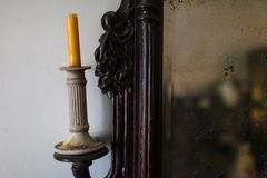 Ancient candlestick with a candle and mirrir with wood carvings royalty free stock image