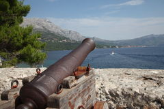 Ancient cannon.  Harbor, Croatia, Korcula. Ancient cannon in Croatia, Korcula island. Sunny day, sea, blue sky, white clouds Royalty Free Stock Photos