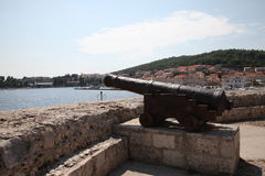 Ancient cannon. Harbor, Croatia, Korcula. Ancient cannon in Croatia, Korcula island. Sunny day, sea, blue sky, white clouds mountains Stock Images