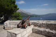 Ancient cannon. Harbor, Croatia, Korcula. Ancient cannon in Croatia, Korcula island. Sunny day, sea, blue sky, white clouds mountains Stock Photos