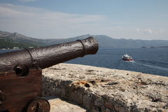 Ancient cannon. Harbor, Croatia, Korcula. Ancient cannon in Croatia, Korcula island. Sunny day, sea, blue sky, white clouds mountains Royalty Free Stock Image