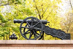 An ancient cannon and a nucleus on the background of oasene foliage. Monument in the form of an ancient cannon royalty free stock image