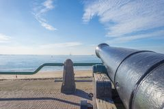 Ancient cannon protecting the coast of the dutch city of Vlissingen below a blue sky. At fall stock images