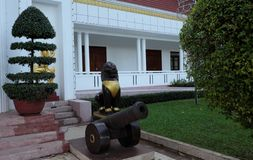Ancient cannon and sculpture of lion, near the steps of the house. Beautifully trimmed bushes. Garden sculpture. Ancient cannon and sculpture of lion, near the royalty free stock photography