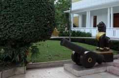 Ancient cannon and sculpture of lion, near the steps of the house. Beautifully trimmed bushes. Garden sculpture. Ancient cannon and sculpture of lion, near the royalty free stock photo
