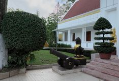 Ancient cannon and sculpture of lion, near the steps of the house. Beautifully trimmed bushes. Garden sculpture.  royalty free stock photography