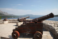 Ancient cannons.  Harbor, Croatia, Korcula. Ancient cannons in Croatia, Korcula island. Sunny day, sea, blue sky, white clouds mountains Stock Photography