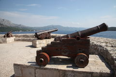 Ancient cannons. Harbor, Croatia, Korcula. Ancient cannons in Croatia, Korcula island. Sunny day, sea, blue sky, white clouds mountains Royalty Free Stock Image