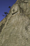 Ancient Carved Buddha relief. Buddhist relief statue carved into the mountainside cliff Royalty Free Stock Image