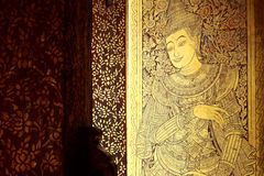 Ancient carved doors covered with lacquer and gold leaves at Wat Royalty Free Stock Photo