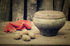 Ancient cast iron pot and potato on a old table in the garden Royalty Free Stock Photography